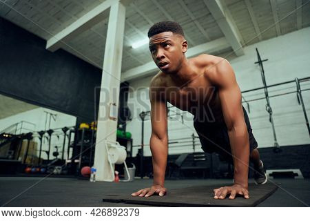 Young African American Male Doing Push-ups In The Gym. Mixed Race, Male Personal Trainer Doing Cross