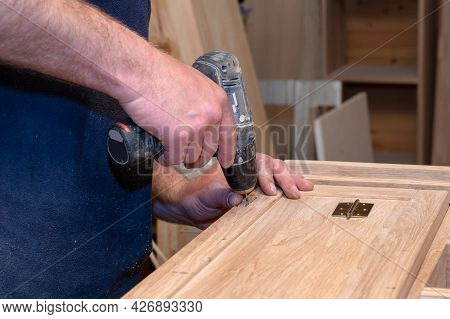 Hands Of A Master Carpenter Install The Hinges On The Cabinet With A Hand-held Power Tool Screwdrive