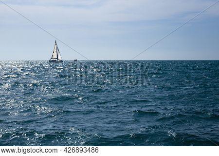 Sailboat On The Horizon At Sea On A Sunny Day