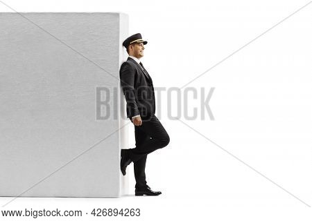 Smiling chauffeur leaning on a wall and waiting isolated on white background