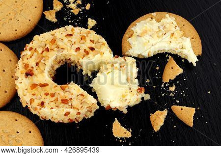 Pineapple Flavour Soft Cream Cheese Ring Coated In Crushed Almonds On A Slate Stone Background