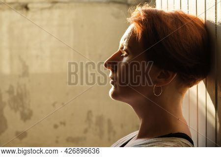 Artistic Portrait Of A Red-haired Woman In Profile. Backlit Portrait Of A Woman. Close-up Of A Pensi