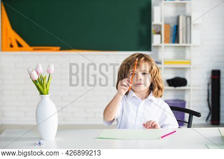 First Grade. Kid Studying At School. Schoolchild Doing Homework At Classroom. Education For Kids.