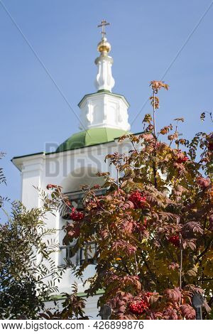 Against The Background Of A Blue Sky, A White Bell Tower With A Green Roof Rises. Bells Are Visible