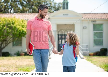 Father And Son Walking Trough School Park. Father And Son Go To School, Education And Learning.