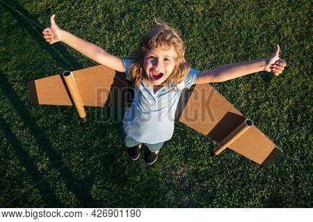 Excited Dreamer Boy Playing With A Cardboard Airplane. Childhood. Fantasy, Imagination. Boy Dreams O