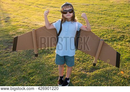 Power Superhero Child Shows Muscles. Boy Dreams Of Flying. Carefree Child Playing Outdoors.
