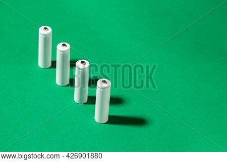 White Aa Batteries On A Green Background. Space For Text. Recycling Of Rechargeable Nimh Batteries.