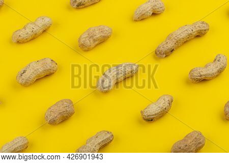 Pattern Of Peanuts With Shell. Fashionable Sunny Pattern Of Peanuts With Shell On Yellow Background.