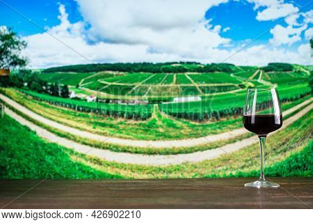 Glass Of Red Wine On In The Vineyard Background. Winemaking Concept. Space For Text.
