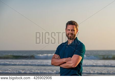 Smiling Man With Crossed Arms By The Sea, Toothy Smile Middle Age Man. Portrait Of Man On Beach.