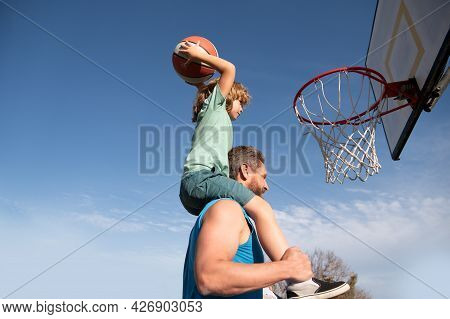Father And Son Playing Basketball. Happy Father Holding His Little Son On Shoulders, Helping Him To