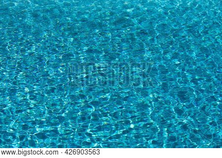Water Background. Blue Water, Ripples And Highlights. Texture Of Water Surface And Tiled Bottom.