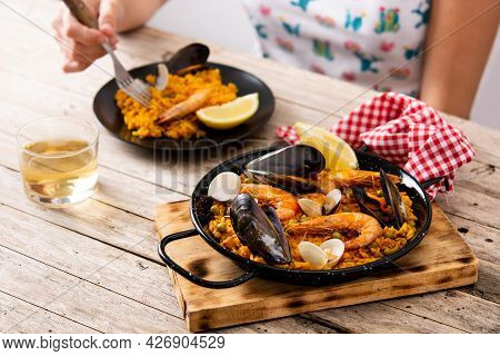 Woman Eating Spanish Seafood Paella On Wooden Table