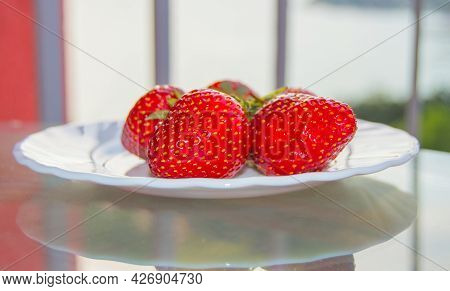 Ripe Red Strawberries On A White Plate, On A Transparent Glass Table