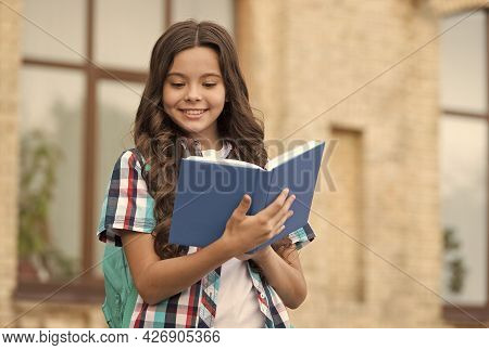 Happy Kid With Long Wavy Hair In Casual Style Read School Book In Schoolyard, Reading