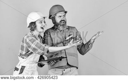 Look Just Perfect. Woman And Man Wear Safety Hardhat. Family Standing Inside House Under Constructio