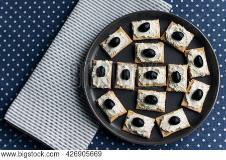 Plate With Crackers With Soft Cheese And Olives On A Blue Polka Dot Tablecloth.