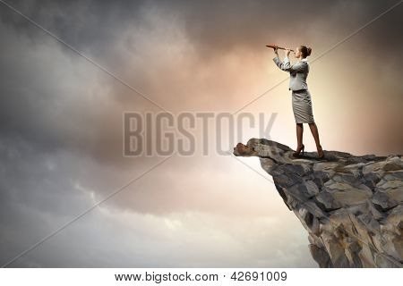 Image of businesswoman looking in telescope standing atop of rock poster