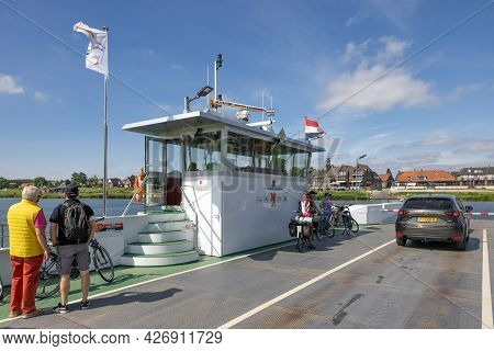 Broekhuizen, The Netherlands - June 19, 2021: Bikers And Car At Ferry Crossing Dutch River Meuse