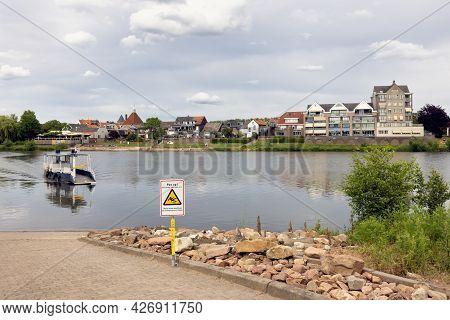 Arcen, The Netherlands - June 20, 2021: Small Ferry Crossing River Meuse Near Dutch Village Arcen