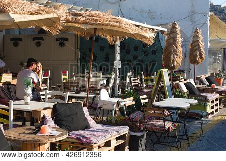 Ios Island - Greece - September 21 2018 : Relaxed Pavement Cafe By The Harbor. Holiday Makers Enjoy