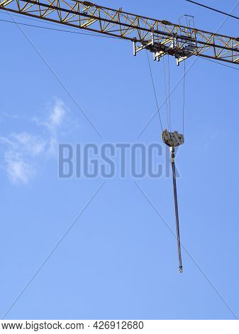 A Lifting Hook With Metal Chains Moves Along The Boom Of A Tower Crane. Industrial Background With B
