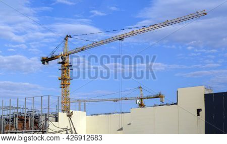 Two Tower Cranes Are Working On The Construction Of A Large Building. Industrial Background With Bui