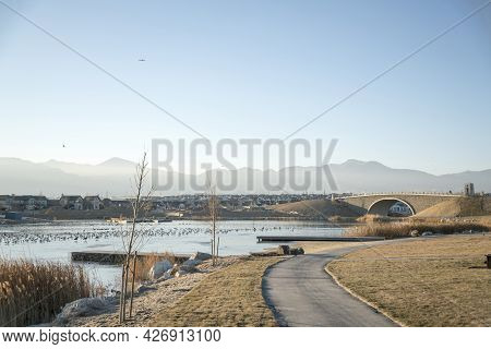 Trail Near The Lake With Two Piers And Flocks Of Birds On The Water