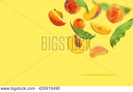 Flying Fresh Ripe Juicy Peaches With Green Leaves On Yellow. Whole And Halved Peaches With Pits, Sli
