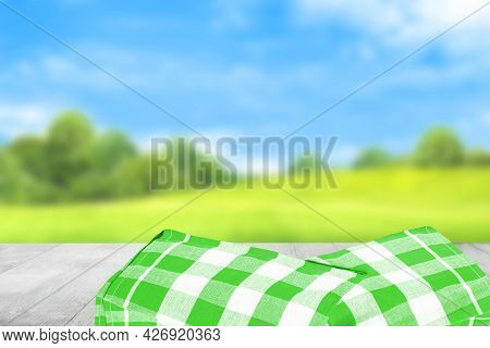 Empty Table Product. Empty Wooden Deck Table Covered With A Green White Checkered Tablecloth Over Ab