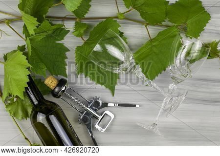 Grape Branches A Wine Corkscrew A Bottle Of Wine And Two Glass Glasses On A Painted Wooden Backgroun