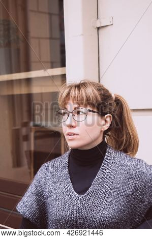 Young Beautiful Woman In Glasses, In A Cozy Gray-blue Vest Spends Time Outdoors