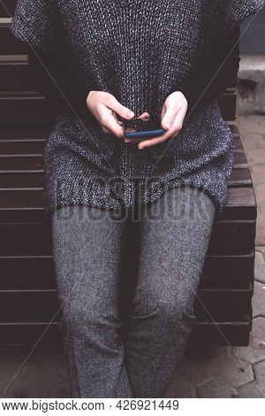 Young Woman In A Cozy Gray-blue Vest Spends Time Outdoors
