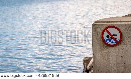 No Swimming Sign Beside Water. Danger Warning.