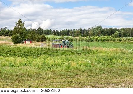 Tractor With A Trailer For Transporting People On The Field. Photo