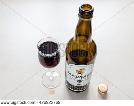 Moscow, Russia - June 10, 2021: Wineglass And Empty Bottle Of Sweet Marsala From Cantine Intorcia. M