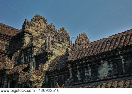 A Fragment Of An Ancient Temple In The Famous Angkor Against The Blue Sky. The Weathered Corrugated