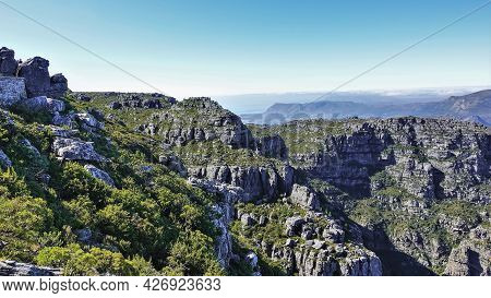 Landscape Of The Top Of Table Mountain In Cape Town. Low Shrubs Grow On The Gray Stones. In The Dist