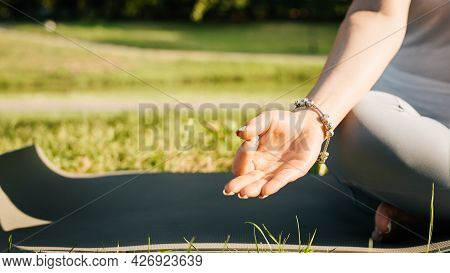 Meditation And Yoga In The Morning Outdoors. Close-up Of A Woman Sitting In A Lotus Position On A Yo