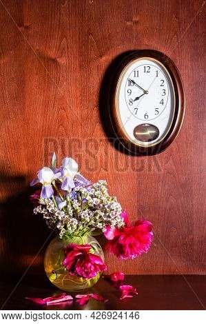 Wall Clock And Withered Flowers In Vase On Dark Brown Wooden Background