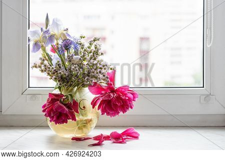 Withered Flowers In Glass Vase On Window Sill At Home With Cityscape On Background