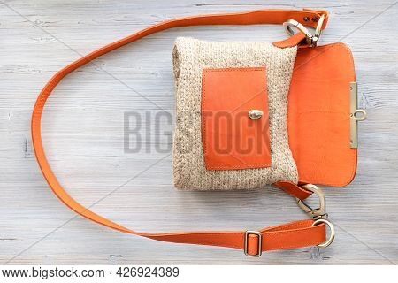 Top View Of Open Hand-knitted Casual Cross Body Bag With Orange Leather Cover On Gray Wooden Table