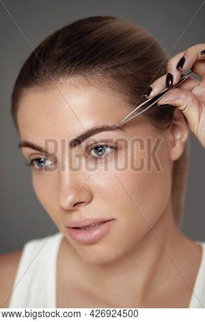 Eyebrow Correction. Beautiful Young Woman Tweezing Eyebrows. Model With Beauty Face Plucking Eyebrow