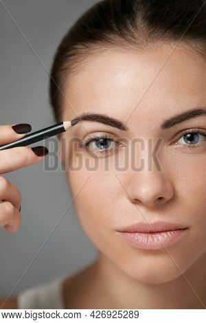Eyebrow Makeup. Beautiful Model Shaping Brows With Brow Pencil Closeup. Beauty Woman With Profession