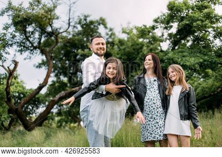 Positive Parents And Their Two Cute Daughters Smiling And Having Fun At Green Summer Park. Father Ho