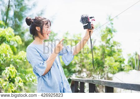 Asian Woman In Blue Dress In Public Park Carrying Digital Mirrorless Camera And Taking Photo And Vlo
