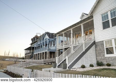 Fenced Luxurious Houses With Elevated Verandas And Front Yard Lawns