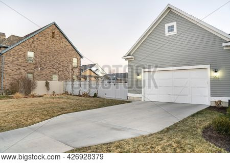 Detached Garage With Closed White Door And Gable Design Exterior
