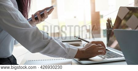 Business Women Hand Are Uses A Smartphone And Use A Laptop Computer In Office.